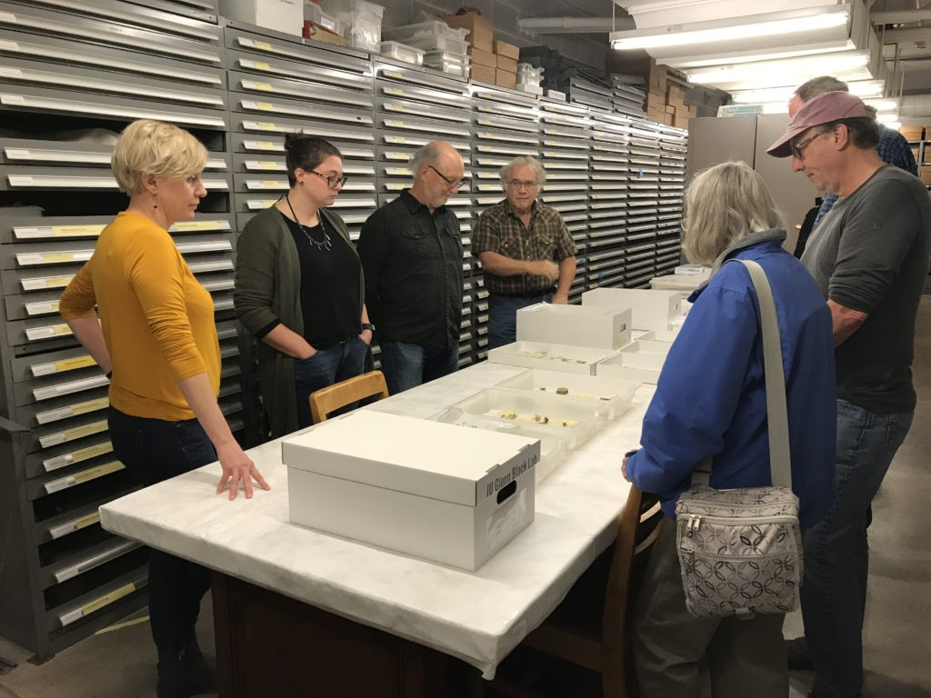 Group of people around artifacts on table in type collection room.