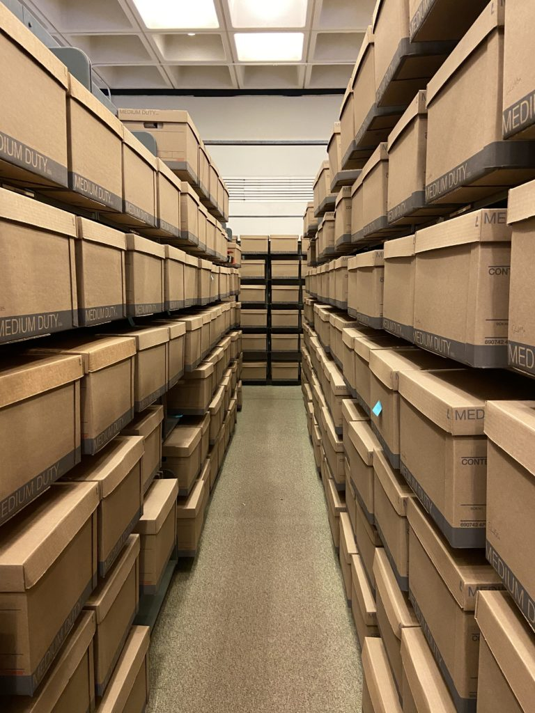 Image down library aisle full of brown boxes.